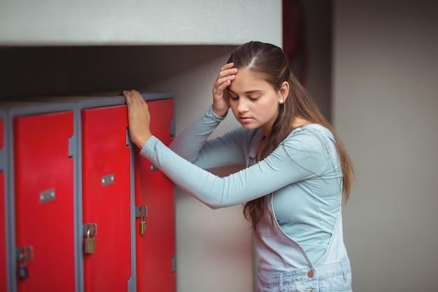 Triest schoolmeisje staande in de kleedkamer