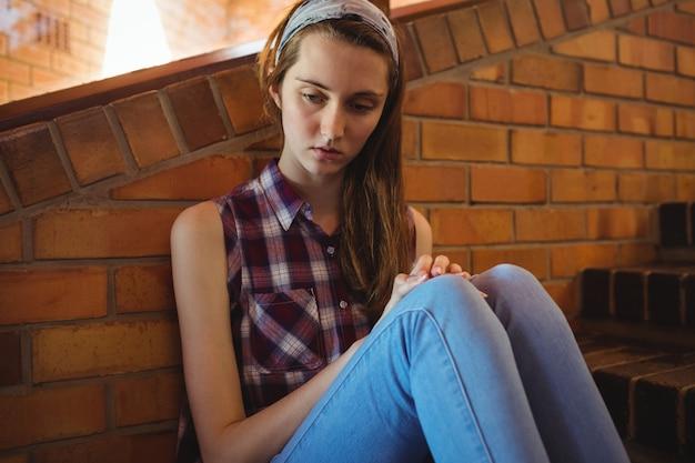 Triest schoolmeisje zit alleen op de trap