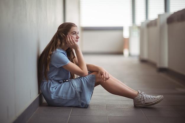 Triest schoolmeisje zit in de gang
