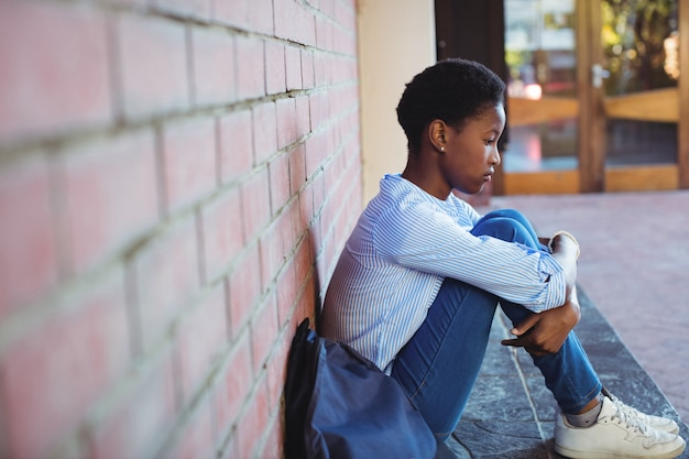 Triest schoolmeisje zittend tegen bakstenen muur