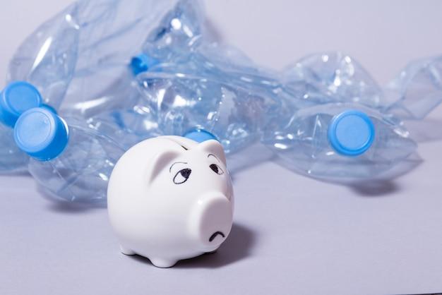 Triest spaarvarken en bos van wegwerp verfrommeld plastic flessen