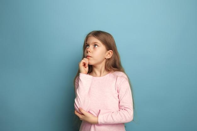 Triest tiener meisje op een blauwe studio achtergrond. gezichtsuitdrukkingen en mensen emoties concept.