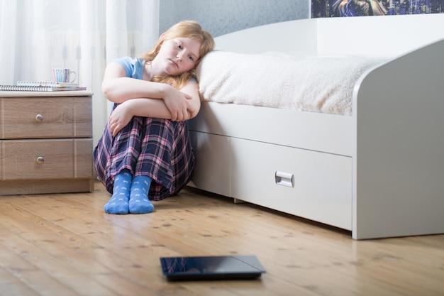 Triest tienermeisje met schalen op de vloer
