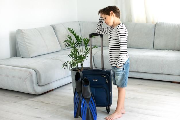 Triest toeristische jongen met een koffer en flippers blijft thuis