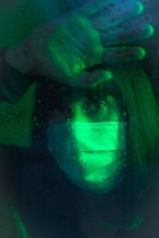 Triest uiterlijk van een jonge blanke brunette met gezichtsmasker kijken naar een regenachtige nacht in de covid19 quarantaine, met groen omgevingslicht