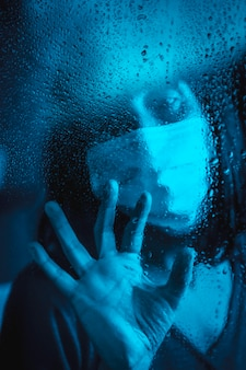 Triest uiterlijk van een jonge blanke brunette met gezichtsmasker kijken naar een regenachtige nacht in de covid19 quarantaine