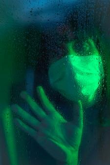 Triest uiterlijk van een jonge blanke brunette met gezichtsmasker op zoek in de quarantaine van de covid19, met groen omgevingslicht