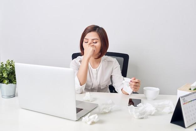 Triest uitgeput vrouw met weefsel die lijden aan koude tijdens het werken met laptop aan tafel