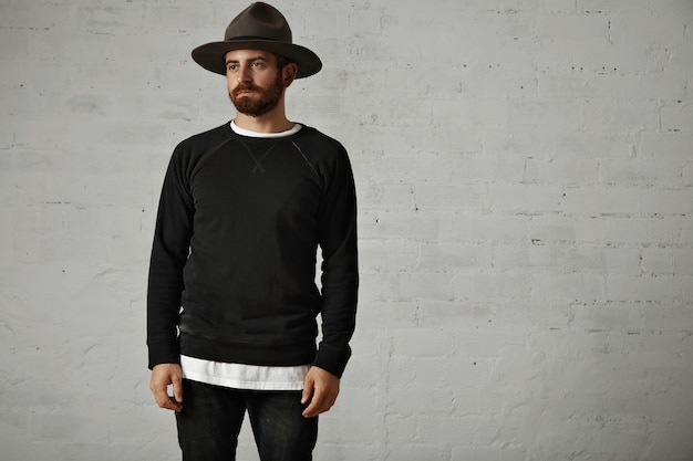 Triest uitziende jonge bebaarde man in een leeg zwart katoenen sweatshirt met lange mouwen en vilten berghoed met witte bakstenen muren