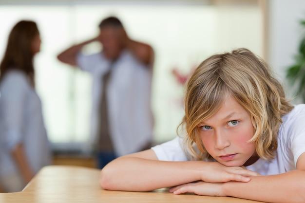Triest uitziende jongen met ruzie ouders achter hem