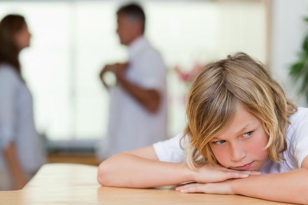 Triest uitziende jongen met vechtende ouders achter hem