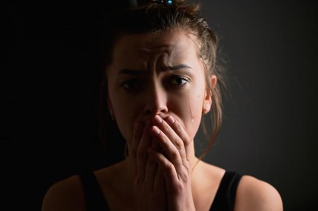 Triest verdriet ellendige wanhopige huilende vrouw met tranen ogen en gevouwen handen