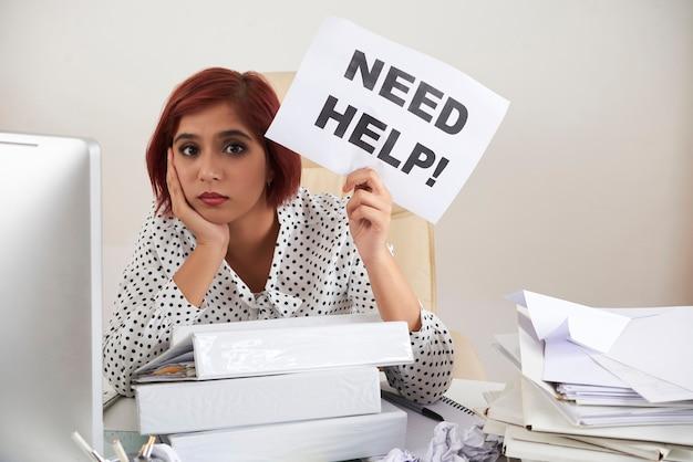 Triest vermoeide zakenvrouw geladen met werk zittend aan tafel met stapels mappen en documenten en s...