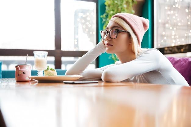 Triest verveeld jonge vrouw zitten aan de tafel in café