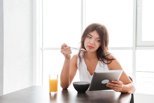 Triest verveelde jonge vrouw die thuis een tablet in de keuken eet en gebruikt