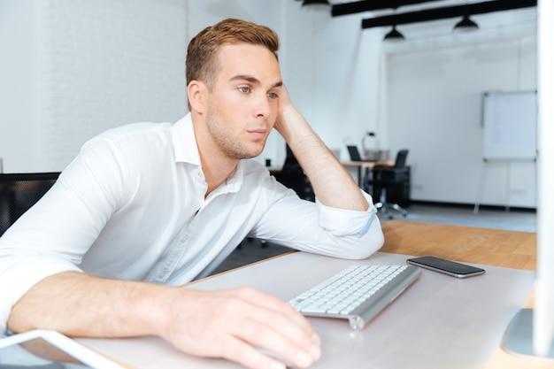 Triest verveelde jonge zakenman die zit en werkt met de computer op kantoor