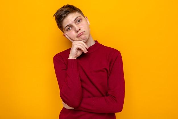 Triest vinger op de wang leggen, jonge knappe kerel die een rode trui draagt