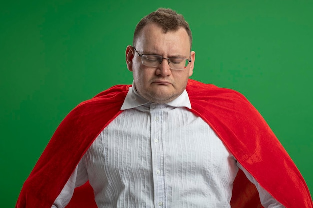 Triest volwassen slavische superheld man in rode cape bril neerkijkt geïsoleerd op groene muur