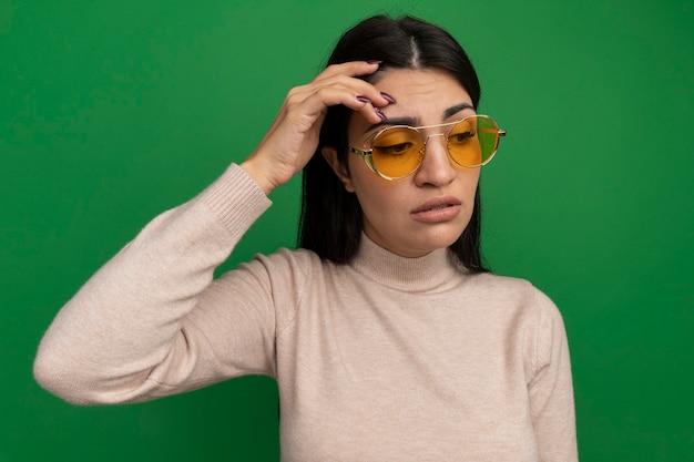 Triest vrij donkerbruin kaukasisch meisje in zonnebril legt hand op voorhoofd op groen