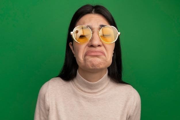Triest vrij donkerbruin kaukasisch meisje in zonnebril staat met gesloten ogen op groen