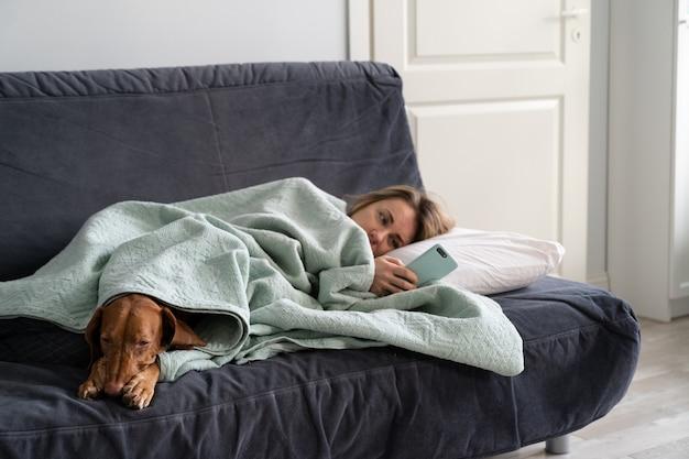 Triest vrouw liggend op de bank met hond, met behulp van slimme telefoon te wachten op vriendje bellen of sms'en, voelt zich depressief