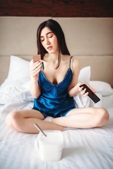 Triest vrouw zittend in bed, mobiele telefoon in handen houdt en snoep eet, vrouwelijke depressie concept. benadrukt meisje dat een probleem heeft