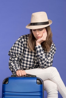 Triest vrouw zittend op blauwe bagage