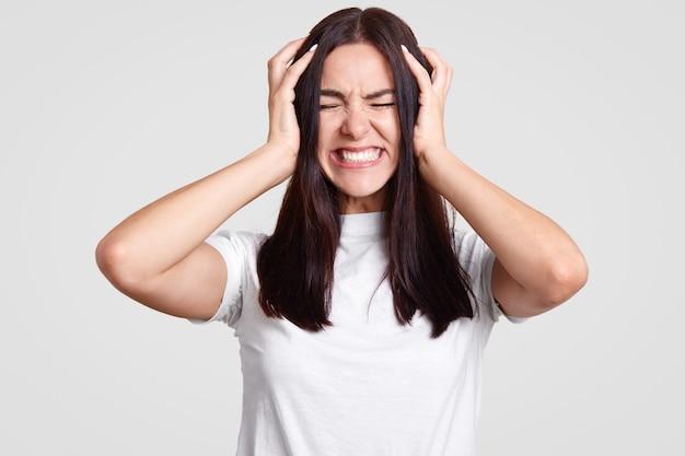 Triest vrouwtje lijdt aan hoofdpijn, houdt de handen op het hoofd, klemt haar tanden op elkaar, heeft een stressvolle uitdrukking, heeft spijt van iets, gaat huilen, draagt een casual outfit, geïsoleerd op wit. negativiteit