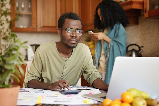 Triest werkloze afrikaanse man met bril met beklemtoonde blik