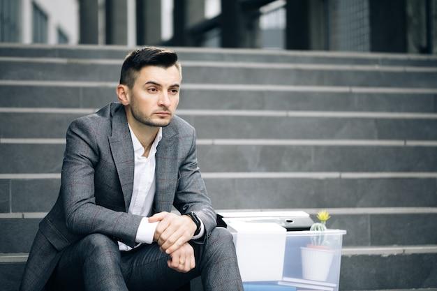 Triest zakenman zittend op trappen buiten met doos spullen als verloren zaken