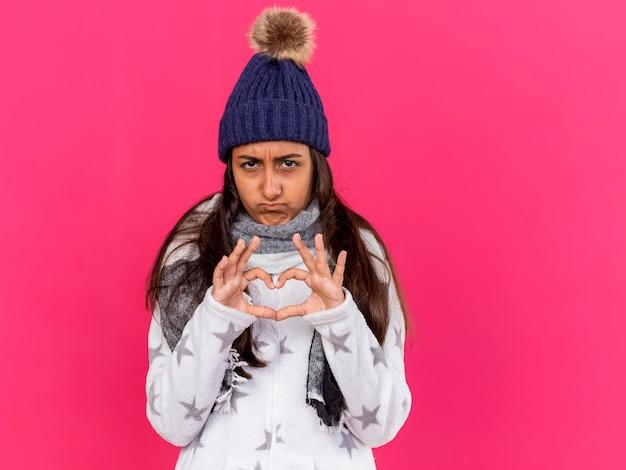 Triest ziek jong meisje dat de winterhoed met sjaal draagt die hartgebaar toont dat op roze wordt geïsoleerd