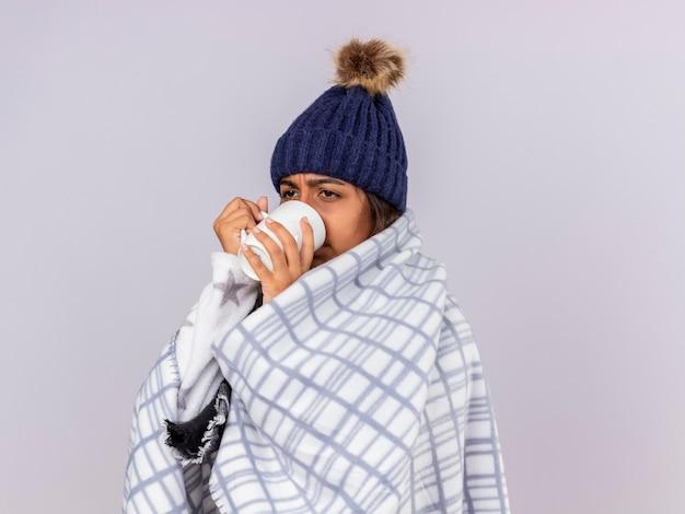 Triest ziek meisje kijken kant dragen winter hoed met sjaal verpakt in plaid drinken thee geïsoleerd op wit