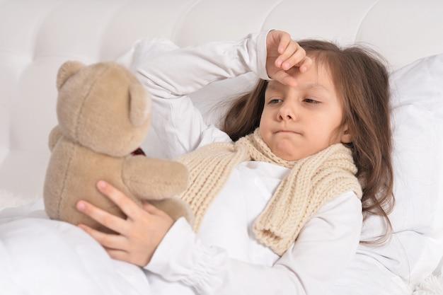 Triest ziek meisje liggend in het bed met teddybeer speelgoed