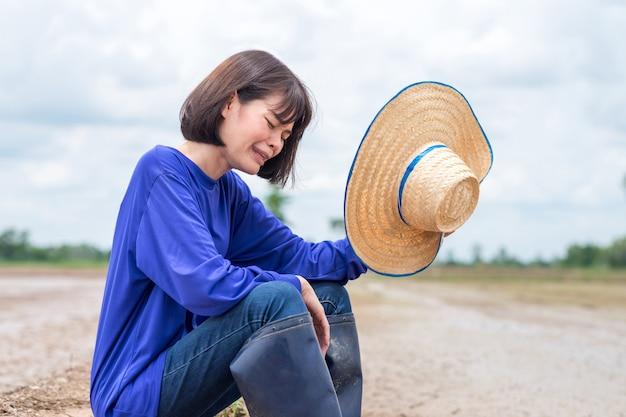 Trieste aziatische boerin zit en huilt teleurgesteld dat ze geen water heeft om rijst te planten op de boerderij