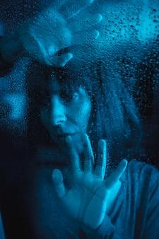 Trieste blik van een jonge blanke vrouw kijken naar een regenachtige nacht in de quarantaine van de covid19