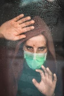 Trieste blik van een jonge man met een masker in de covid-19 pandemie kijkend door een raam