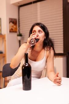 Trieste en depressieve vrouw die zelf rode wijn drinkt, zittend aan de keukentafel. ongelukkige persoon ziekte en angst gevoel uitgeput met alcoholisme problemen.