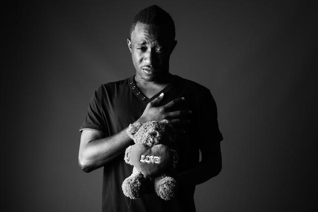 Trieste jonge afrikaanse man met teddybeer en liefde tekentekst in zwart-wit