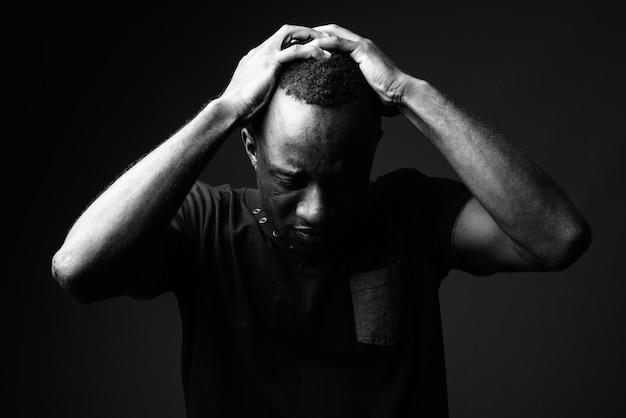 Trieste jonge afrikaanse man tegen zwarte muur in zwart-wit