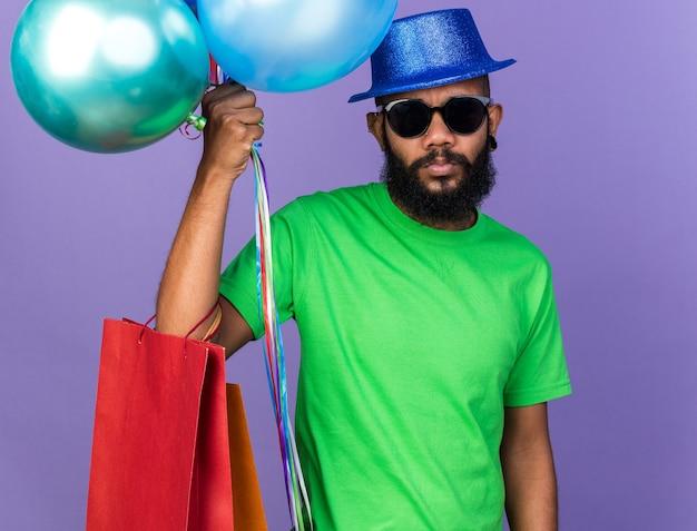 Trieste jonge afro-amerikaanse man met een feestmuts met een bril die ballonnen vasthoudt met een cadeauzakje geïsoleerd op een blauwe muur