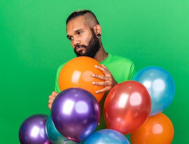 Trieste jonge afro-amerikaanse man met een groen t-shirt dat achter ballonnen staat