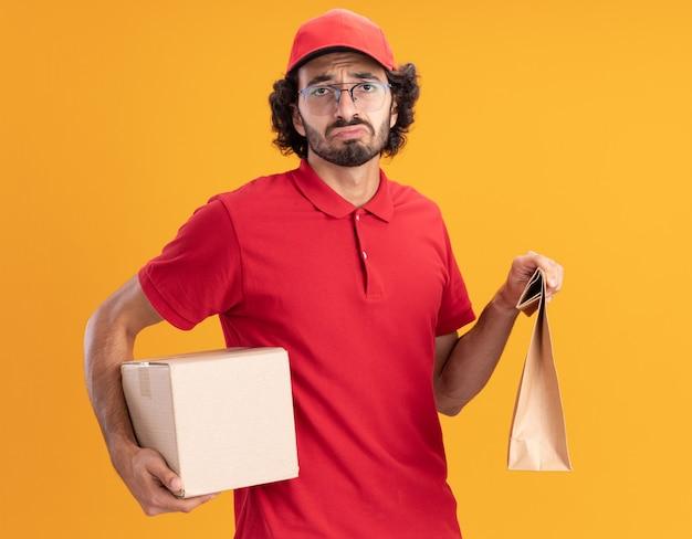 Trieste jonge bezorger in rood uniform en pet met een bril met een kartonnen doos en een papieren pakket kijkend naar de voorkant geïsoleerd op een oranje muur