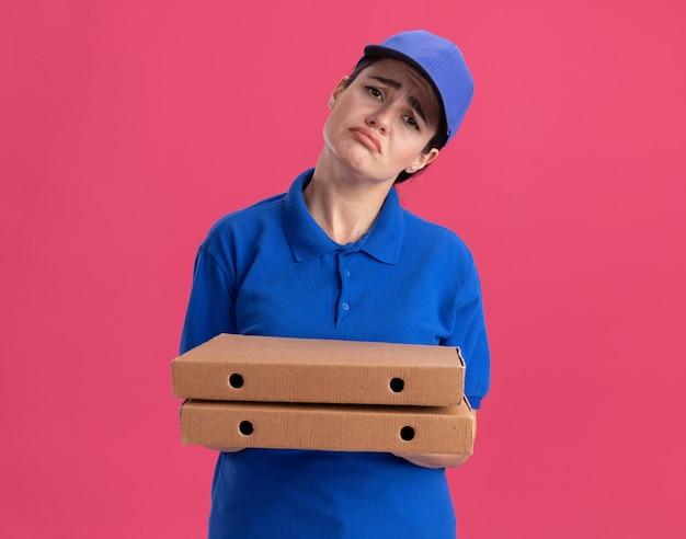 Trieste jonge bezorger in uniform en pet met pizzapakketten geïsoleerd op roze muur met kopieerruimte
