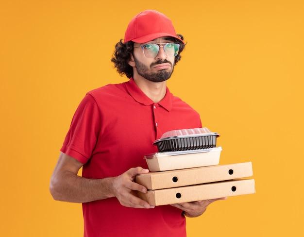 Trieste jonge blanke bezorger in rood uniform en pet met bril met pizzapakketten met papieren voedselpakket en voedselcontainer erop kijkend naar camera geïsoleerd op oranje achtergrond