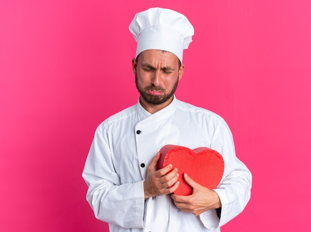 Trieste jonge blanke mannelijke kok in uniform van de chef en pet met hartvorm huilend met gesloten ogen geïsoleerd op roze muur