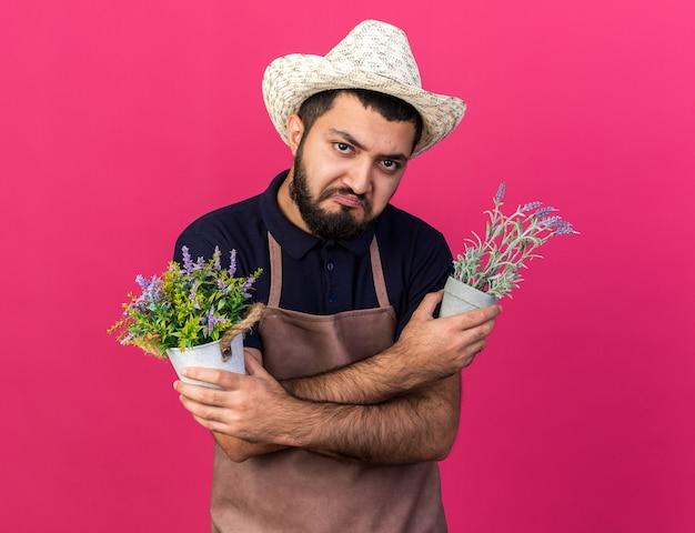 Trieste jonge blanke mannelijke tuinman met een tuinhoed met bloempotten die armen kruisen geïsoleerd op een roze muur met kopieerruimte