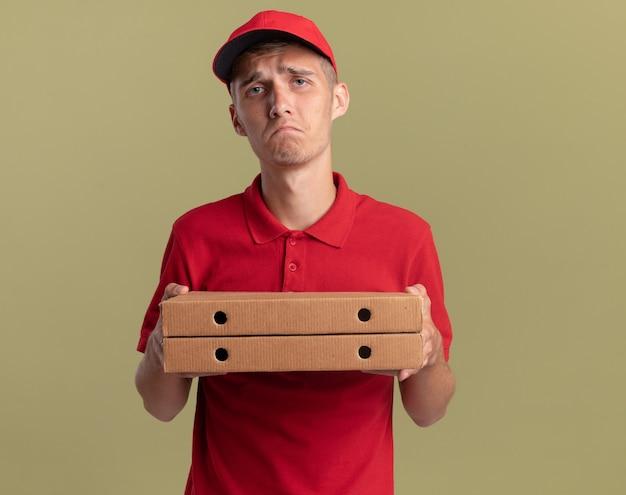 Trieste jonge blonde bezorger houdt pizzadozen vast