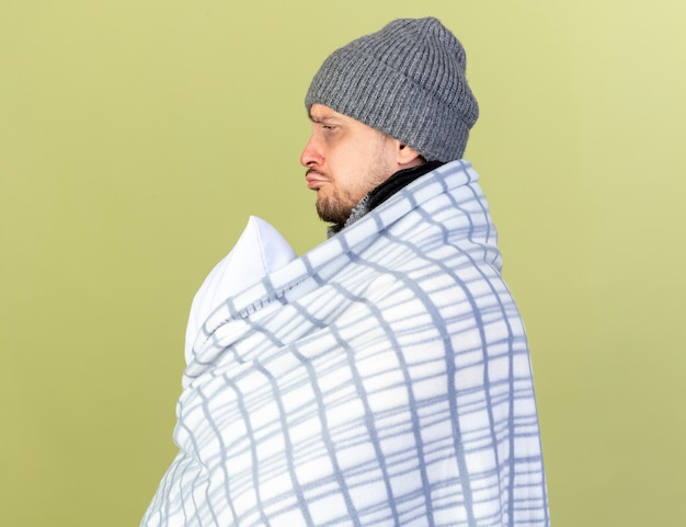 Trieste jonge blonde zieke man met muts en sjaal gewikkeld in plaid staat zijwaarts met kussen geïsoleerd op olijfgroene muur