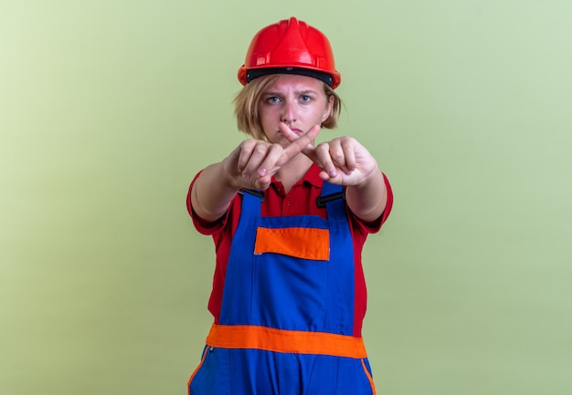 Trieste jonge bouwvrouw in uniform met gebaar van nee geïsoleerd op olijfgroene muur