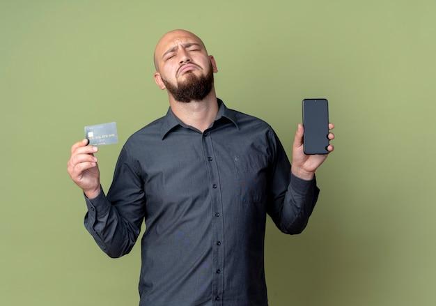 Trieste jonge kale call center man met mobiele telefoon en creditcard met gesloten ogen geïsoleerd op olijfgroene muur